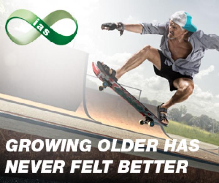 Elderly man jumping on a skateboard a skate park