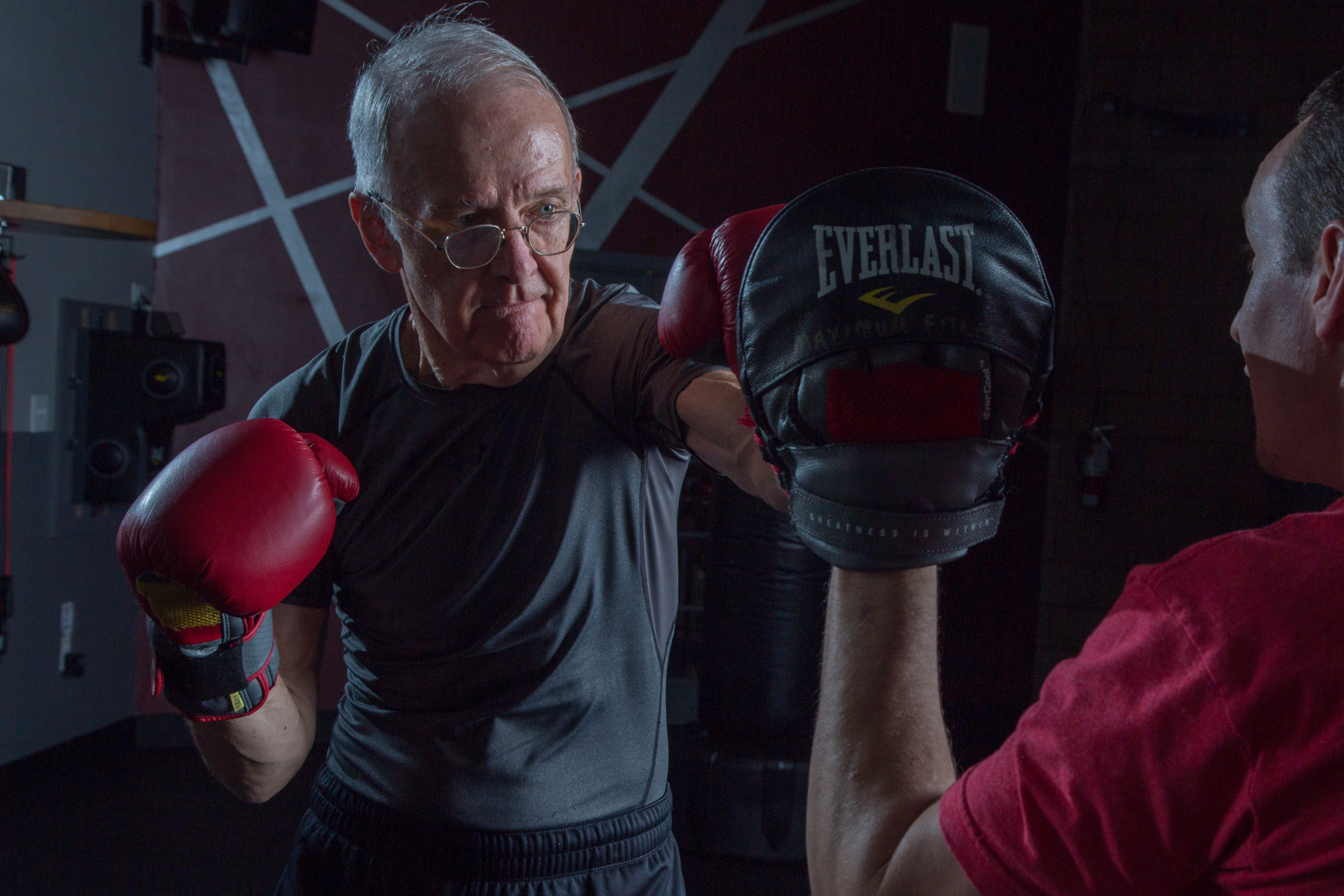 Elderly man boxing with a coach