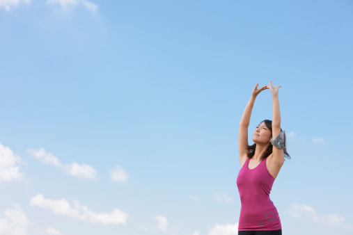 Woman with brown hair and a pink top stretching up in front of the sky