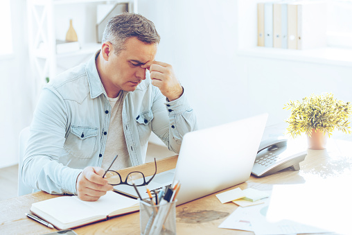 Man sitting at a desk and feeling stressed about his laptop