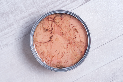 A downward view of a tin filled with tuna