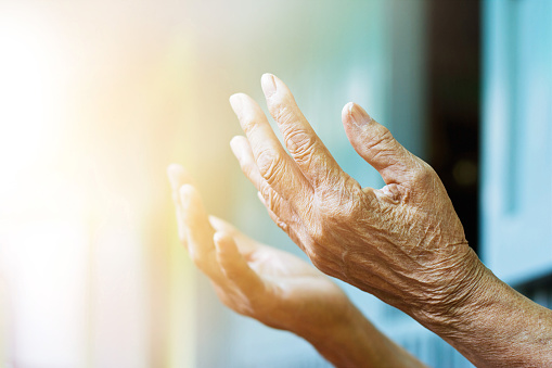 Elderly hands lifting up to a light