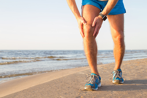 Man running on the beach holding his knee in pain