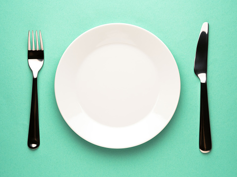An empty plate in-between a knife and fork on a blue background