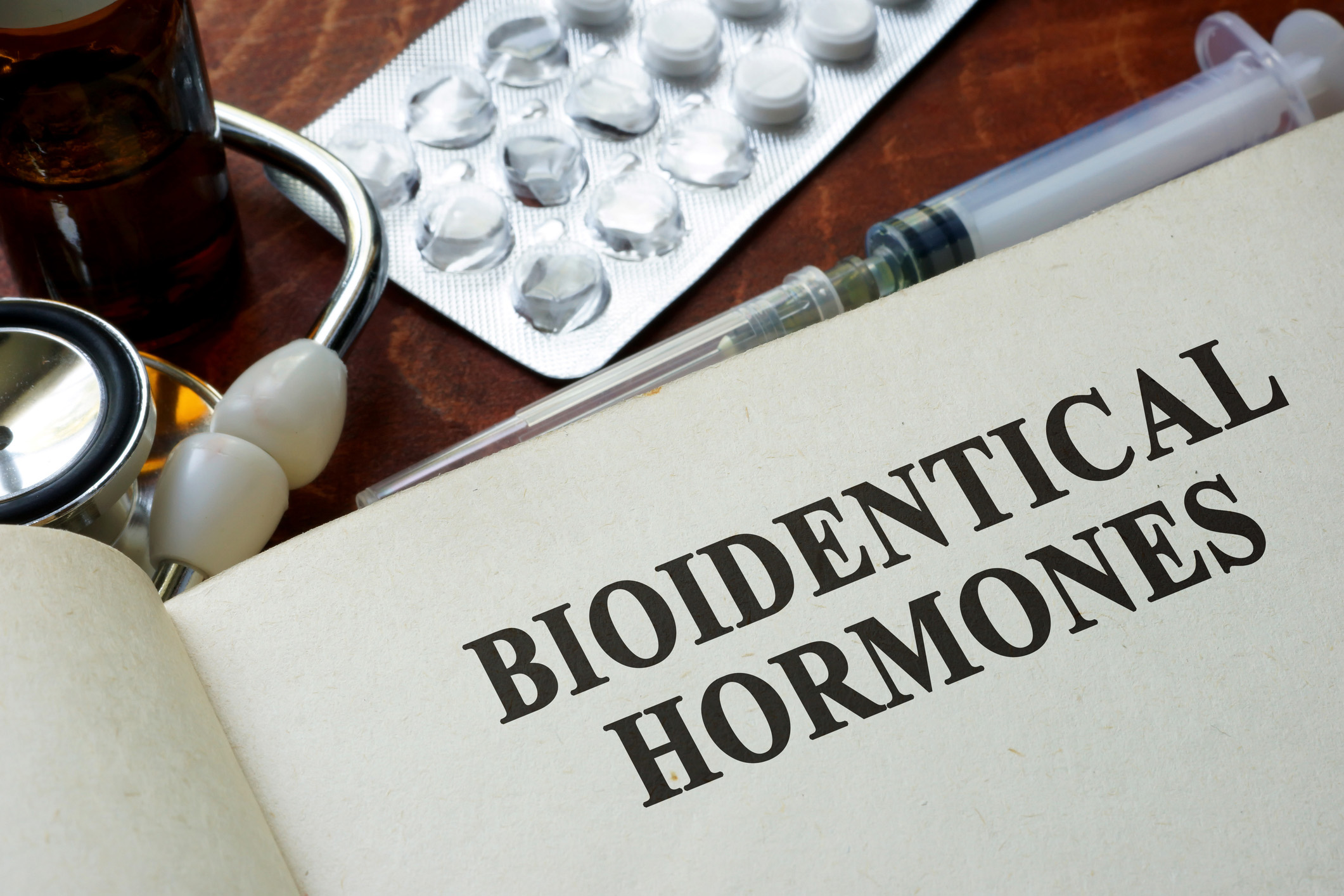 A book of Bioidentical Hormones next to a syringe, stethoscope and pack of pills