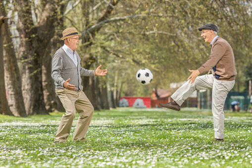 Two elderly men playing football in a park