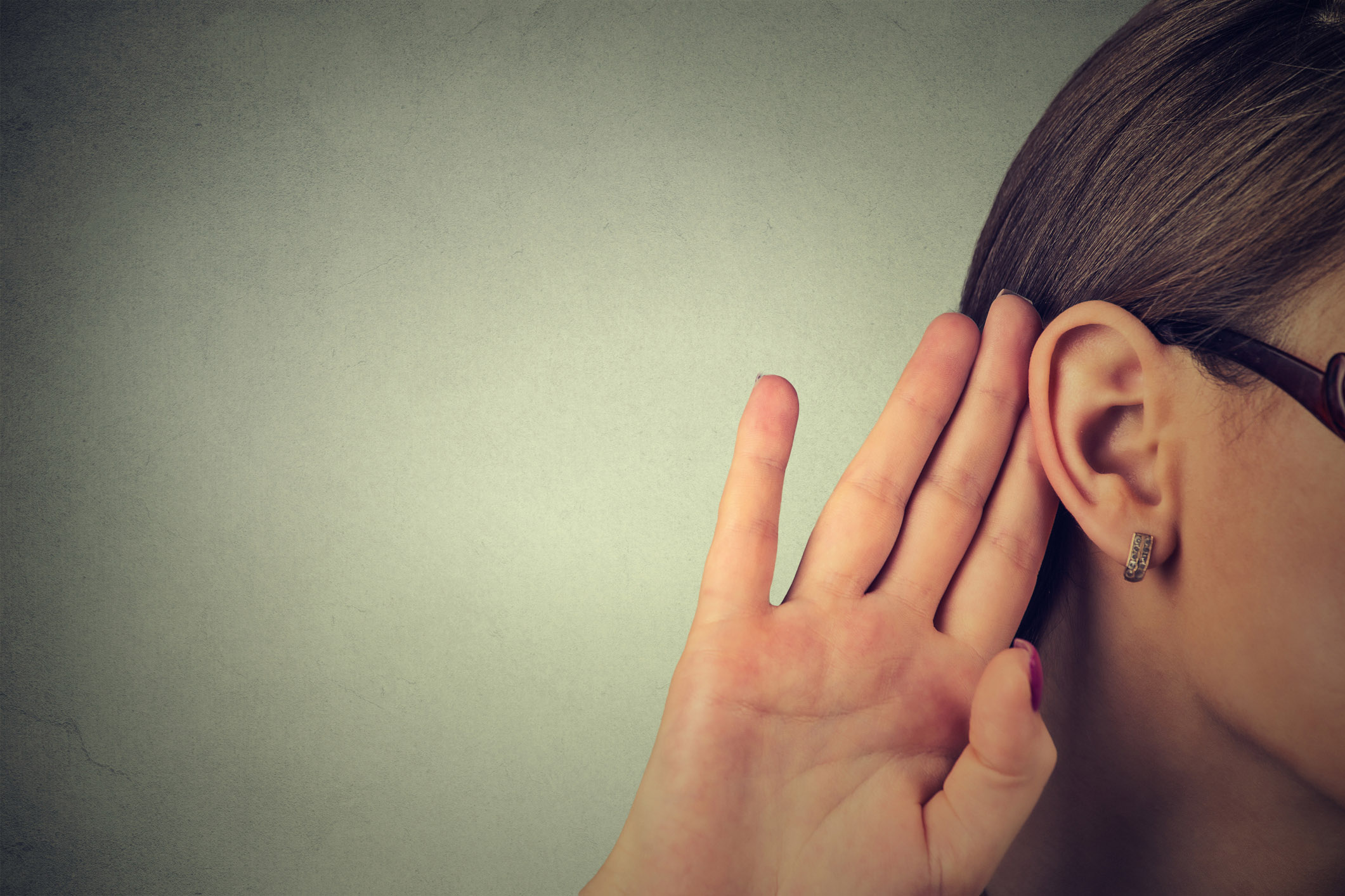 A woman cupping her ear to hear better