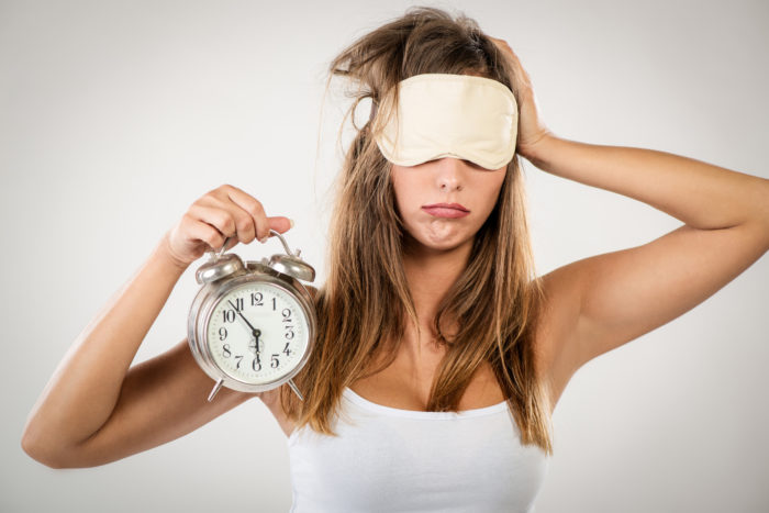 A woman holding an alarm clock and wearing a sleep mask