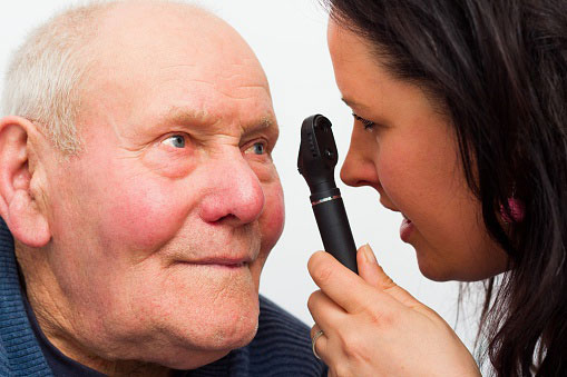 A woman looking into an elderly mans eye using a tool
