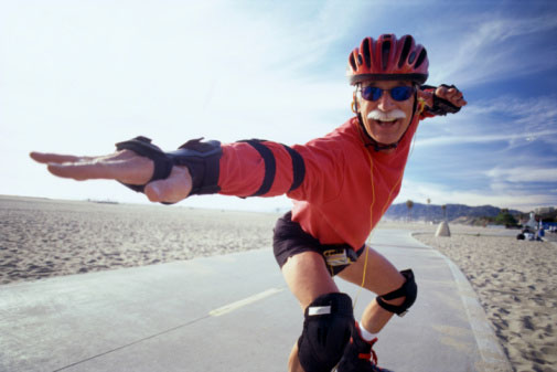 Elderly man rollerblading next to a beach wearing protective gear