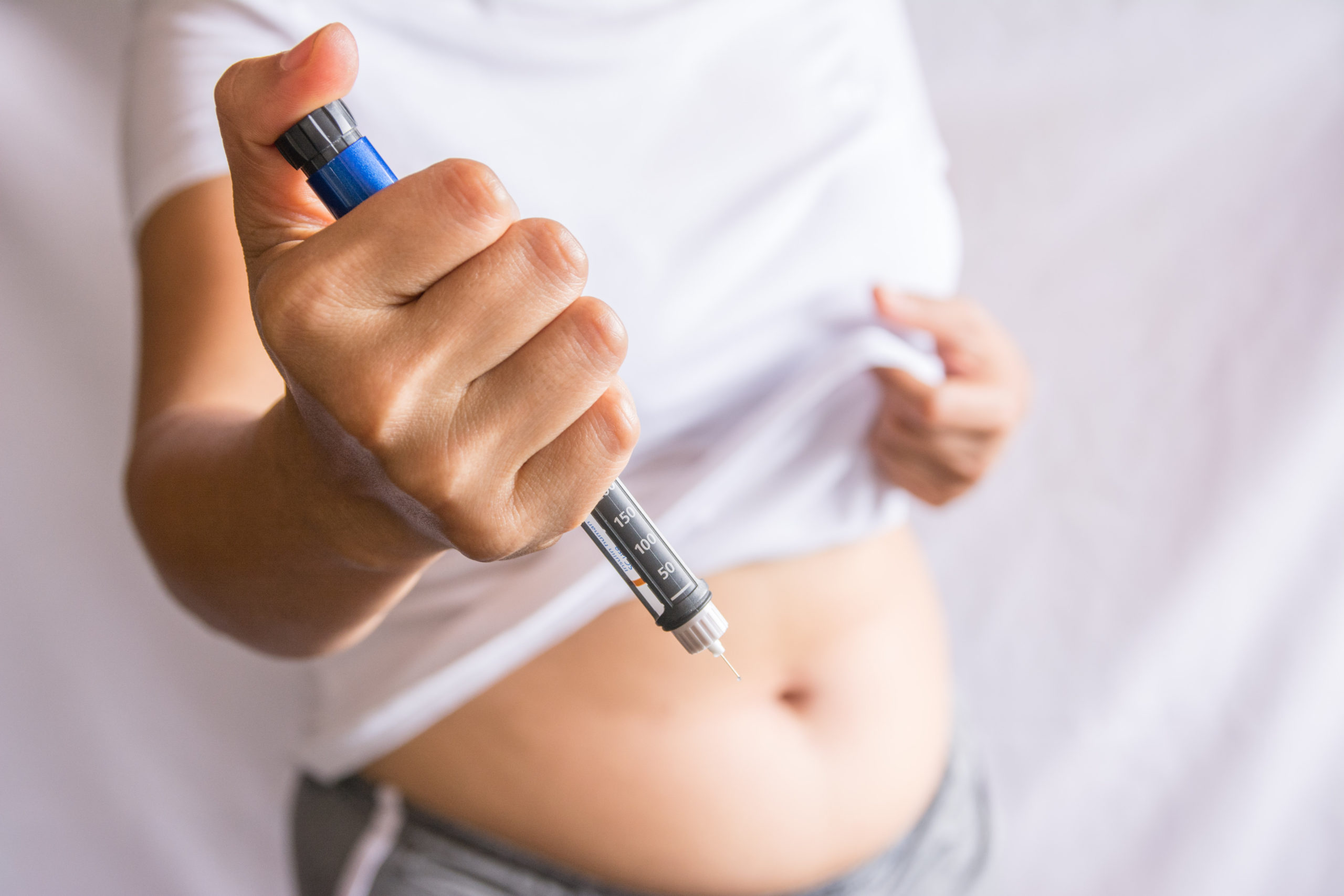 A person holding up an EpiPen, getting ready to inject into their stomach