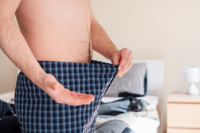 A man looking down into his underwear confused