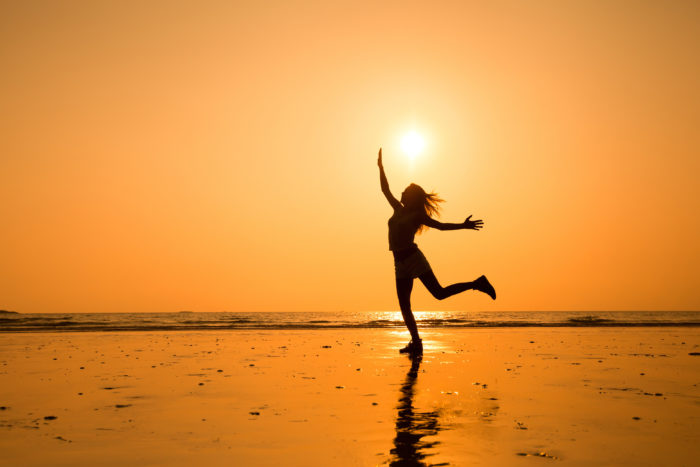 Woman jumping on the beach Infront of the sunset