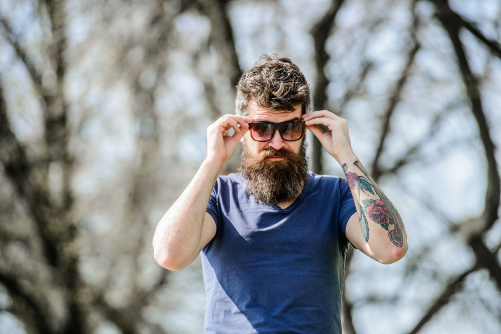 Man with blue t-shirt and large beard putting sunglasses on