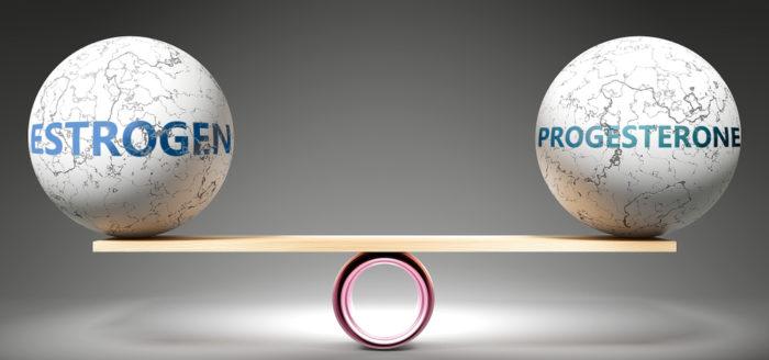 Estrogen ball and progesterone ball balancing on wood