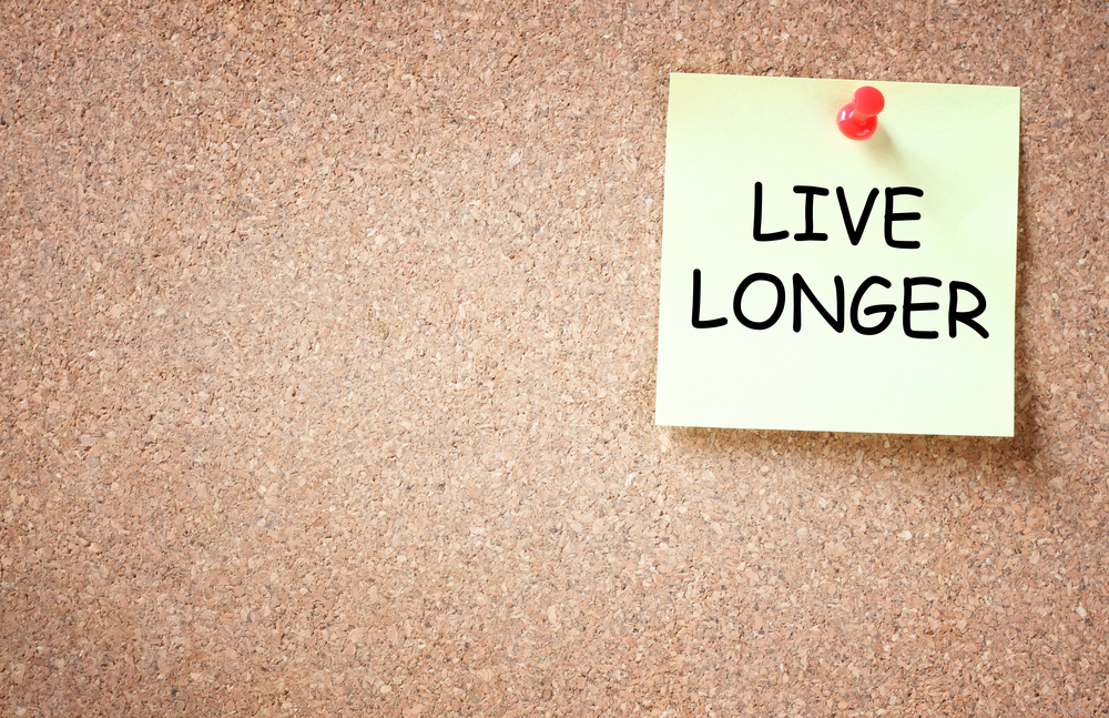Sticky note pinned on a cork board with the text 'Live Longer'