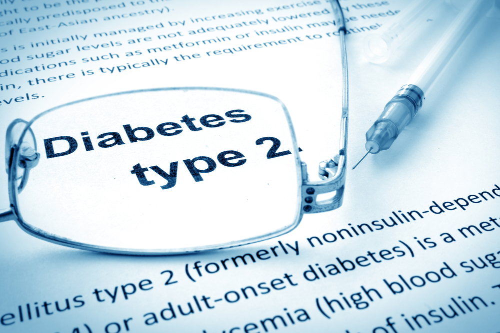 Diabetes Type 2 text on paper magnified with glasses next to a syringe