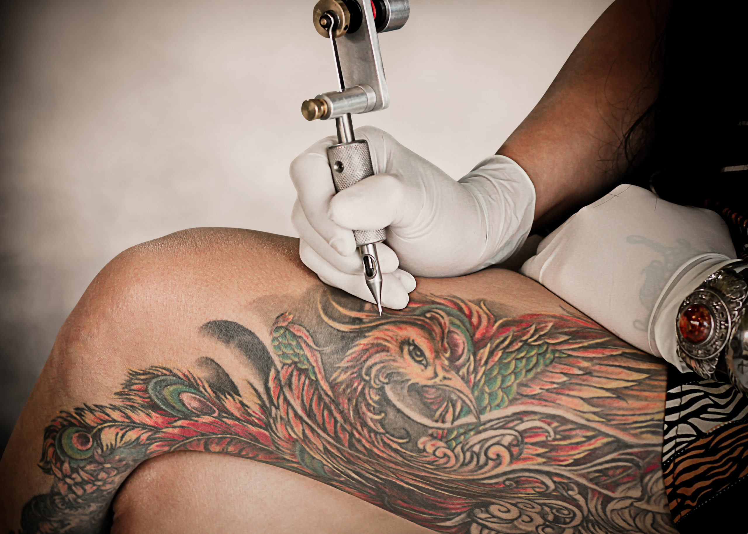 Somebody tattooing a leg with a tattoo gun