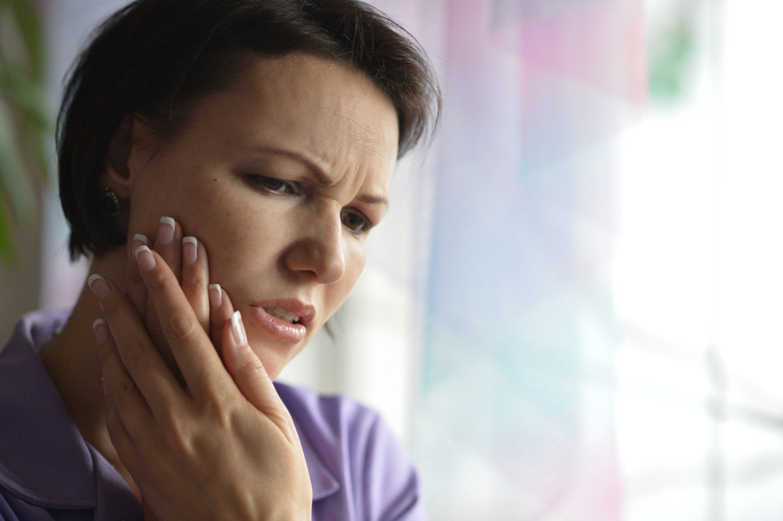 A woman with dark brown short hair holding her cheek because of tooth pain