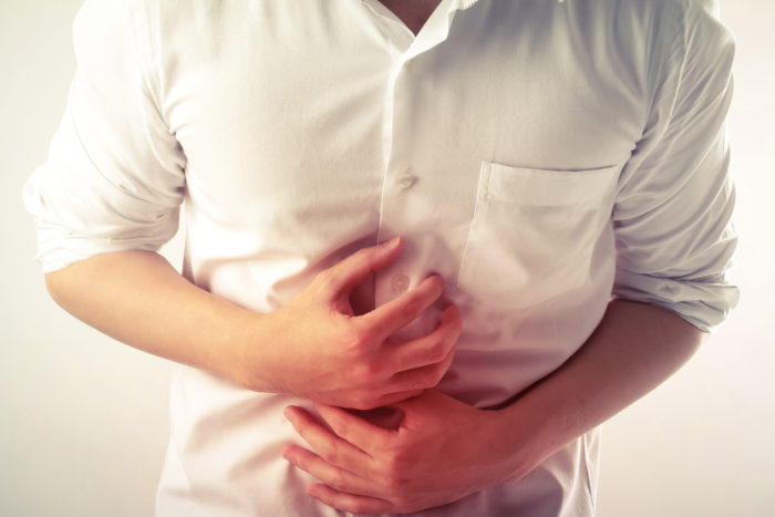 Person in a white shirt in pain with their stomach