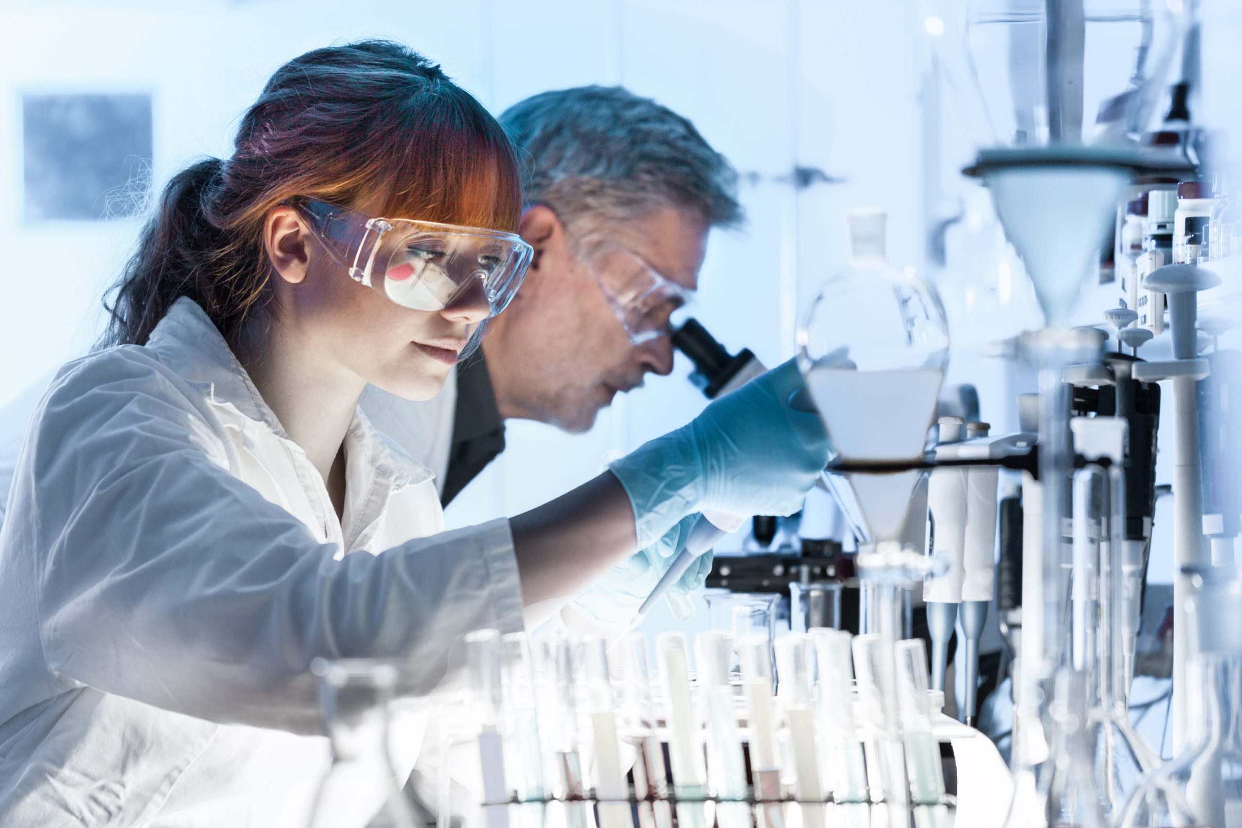 Woman and man wearing lab coats using microscopes in a lab