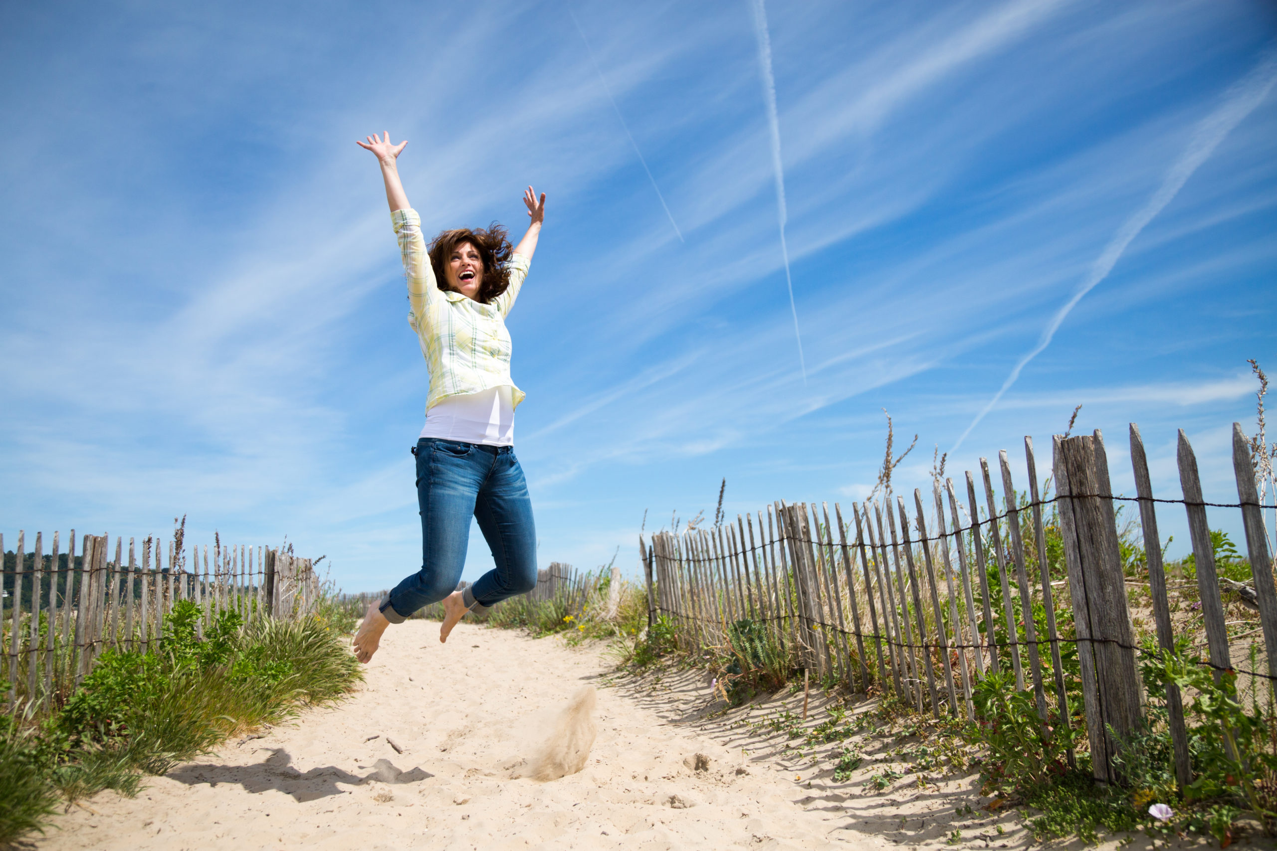 Woman jumping on a sandy beach wearing a yellow shirt and jeans