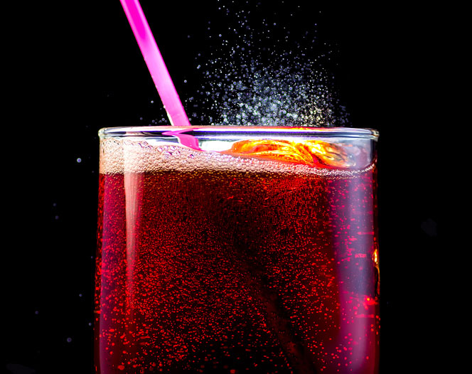 Close up of fizzy soda with a pink straw
