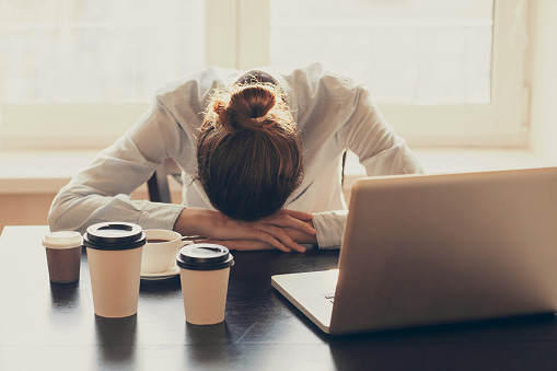 Woman falling asleep in front of her computer surrounded by coffee
